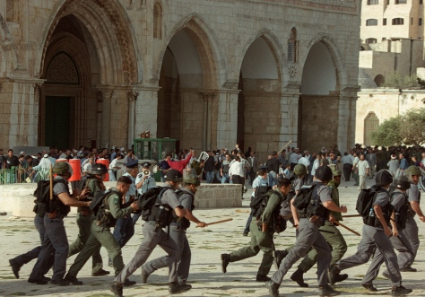 Israeli troops run as clashes erupt outside the Al-Aqsa mosque compound in Jerusalem's Old City 28 September 2000, following a visit to the holy site by Israeli right-wing opposition leader Ariel Sharon. The visit of Israel's current prime minister to Islam's third holiest shrine sparked the outbreak of the second intifada. Exhausted by a conflict both know they are incapable of winning, Israelis and the Palestinians are marking the fifth anniversary of this intifada 28 September 2005. AFP PHOTO/AWAD AWAD (Photo credit should read AWAD AWAD/AFP/Getty Images)